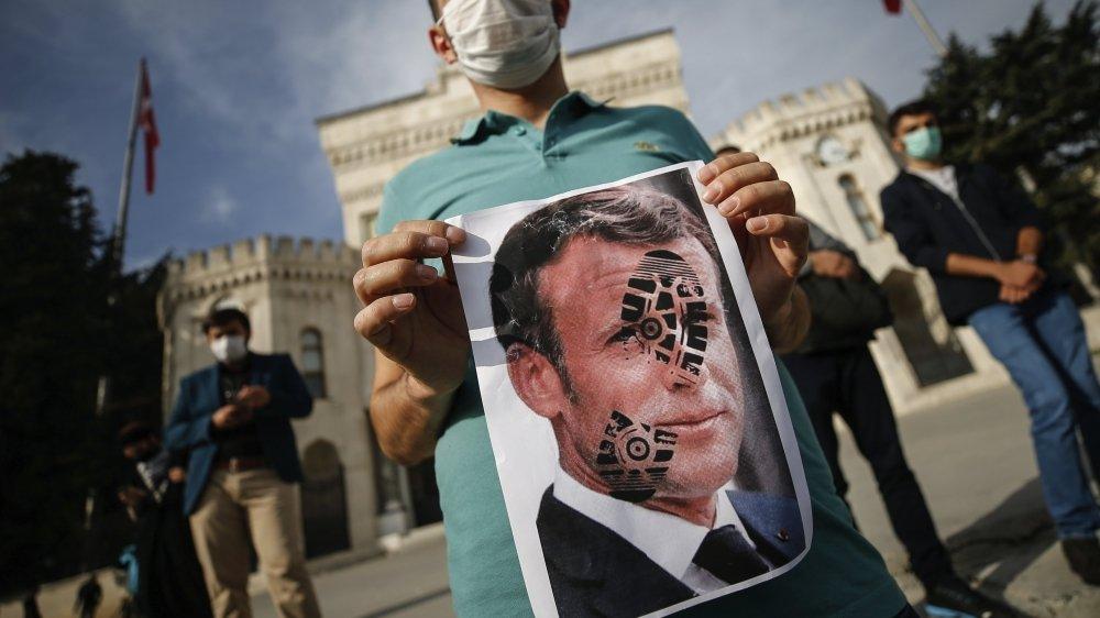 Un jeune tient une image du président français macron marqué d'une trace de chaussure en travers de la figure, en signe de soutien au président turc Recep Tayyip Erdogan, qui l'a attaqué avec des mots violents.