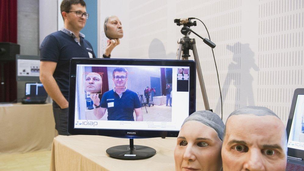 Le docteur Sébastien Marcel montre les masques utilisés pour tester la vulnérabilité du système de reconnaissance biométrique faciale.