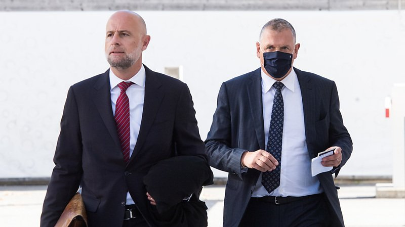 Jérôme Valcke (masqué) arrive avec son avocat au Tribunal pénal fédéral.