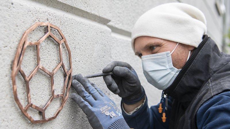 Un ouvrier a installé jeudi une plaque commémorative sur la maison où Köbi Kuhn a grandi à Zurich.