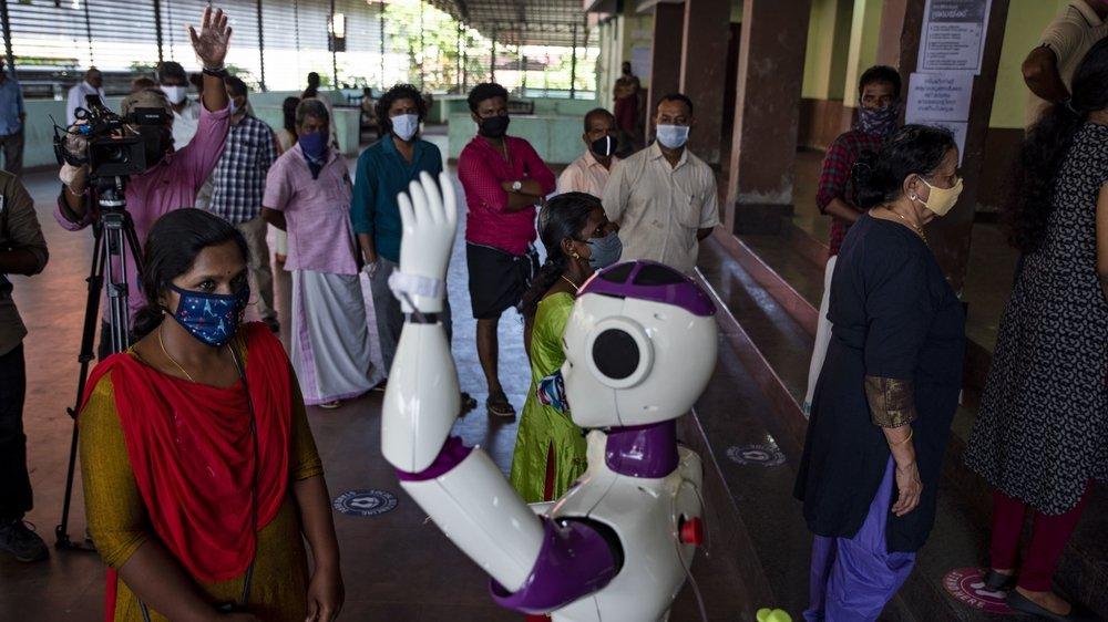 En Inde, un robot prend la température à l'entrée d'un bureau de vote, à Kochi, dans l'Etat du Kerala.