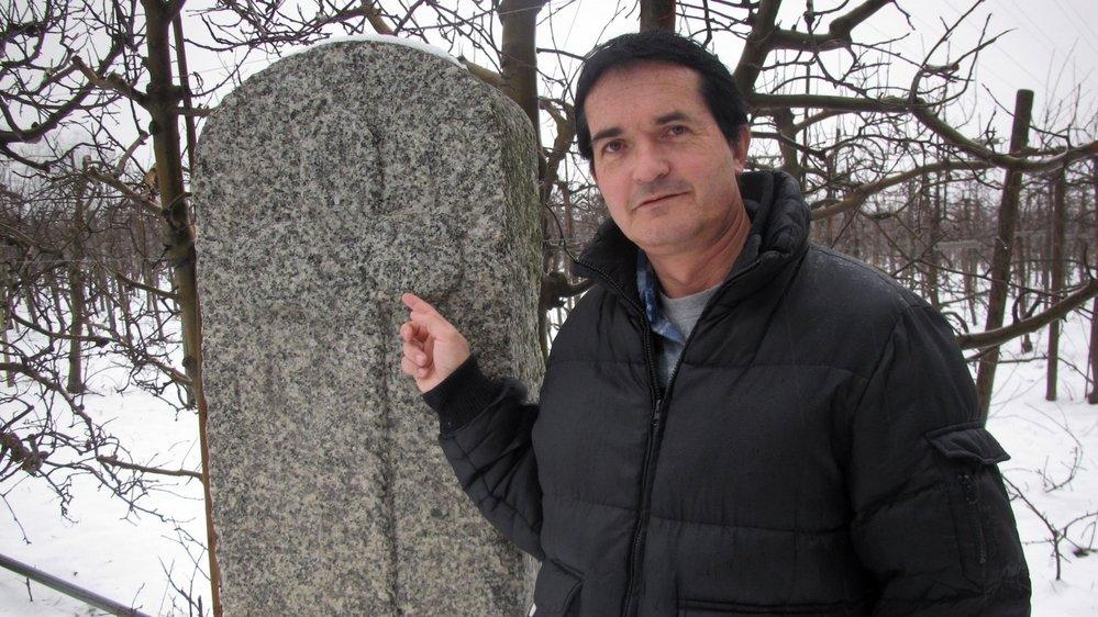 L'archéologue et historien Jean-Christophe Moret auprès de la mystérieuse stèle en granit de Charrat, dans laquelle une croix latine a été taillée.