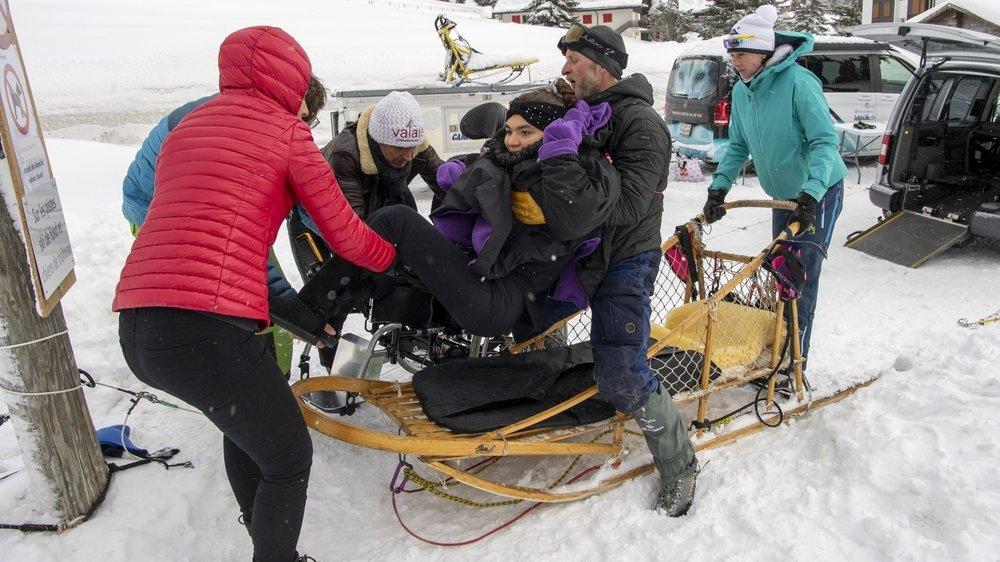 Le transfert du fauteuil au traîneau: une étape périlleuse qui nécessite plusieurs paires de bras.