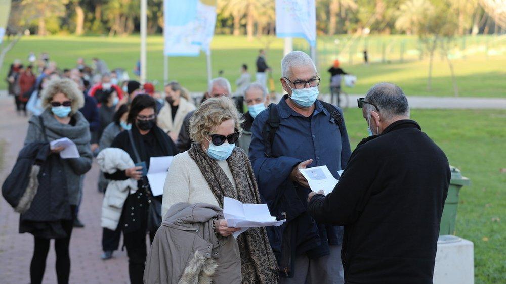 """Des Israéliens font la queue pour présenter leur certificat de vaccination ou leur """"badge vert"""" avant un concert à Tel-Aviv."""