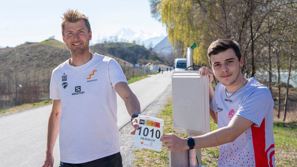 Lucien Epiney et Pierre Cordonier tiennent un dossard devant la borne de départ, près d'Ecossia.
