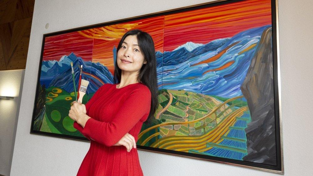 L'artiste chinoise Yi Chen devant la fresque réalisée en hommage au village de Lens.