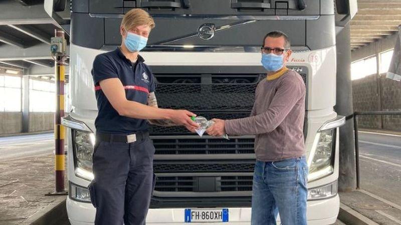 Valérie Roos, membre des pompiers péagistes du tunnel du Grand-Saint-Bernard, offre une saucisse et une bouteille d'eau à un routier italien en transit.