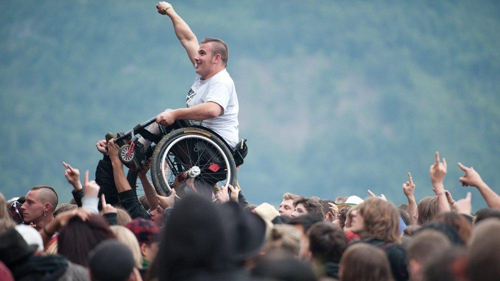 Personne en chaise portée par la foule lors d'un concert à l'Openair de St-Gall.