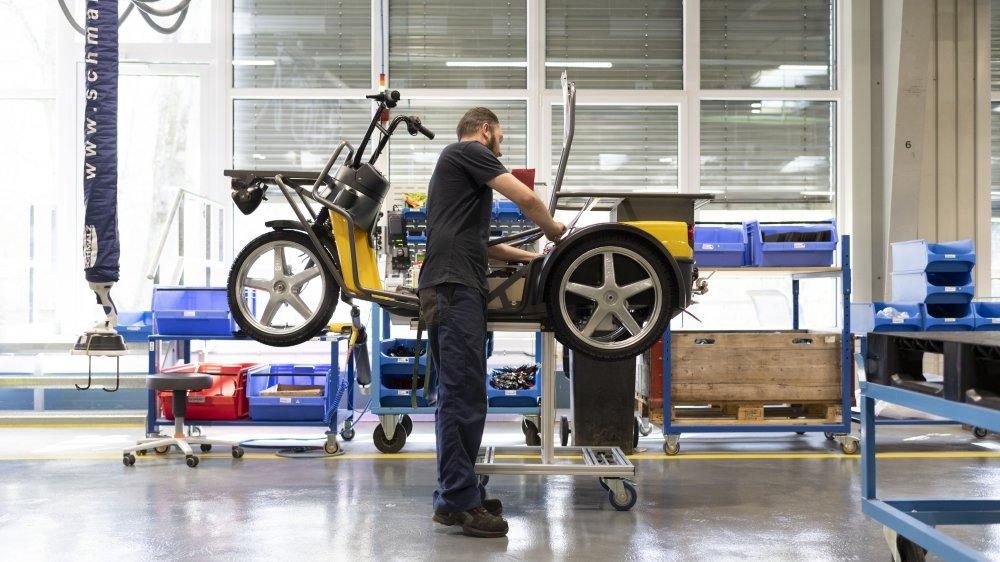 Un employé de la firme zurichoise Kyburz installe une batterie électrique sur un véhicule de La Poste.