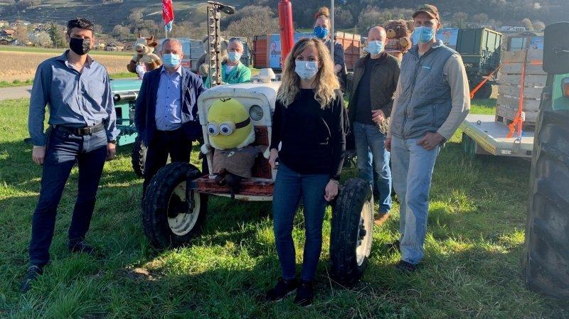 """Les Valaisans ont rallié Villy et le domaine d'Annie Schütz (ici au volant d'un tracteur d'époque décoré) pour lancer la campagne """"2 x non aux initiatives phytos extrêmes"""". On reconnaît derrière leurs masques: Yannick Buttet (président de l'IFELV), Willy Giroud (président de la Chambre valaisanne d'agriculture), Laurent Ecoeur (maître-fromager), Malika Pannatier (technicienne en alimentation du bétail), Olivier Borgeat (secrétaire général de l'IFELV) et Stéphane Angst (agriculteur à Illarsaz)."""