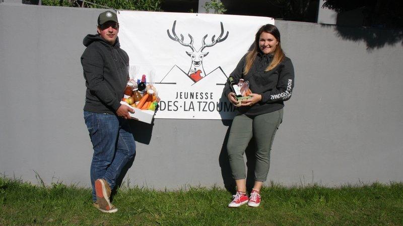 Régis Ançay et Lorélie Monnet, de la Jeunesse de Riddes-La Tzoumaz, présentent le panier solidaire qui vient d'être mis en vente.