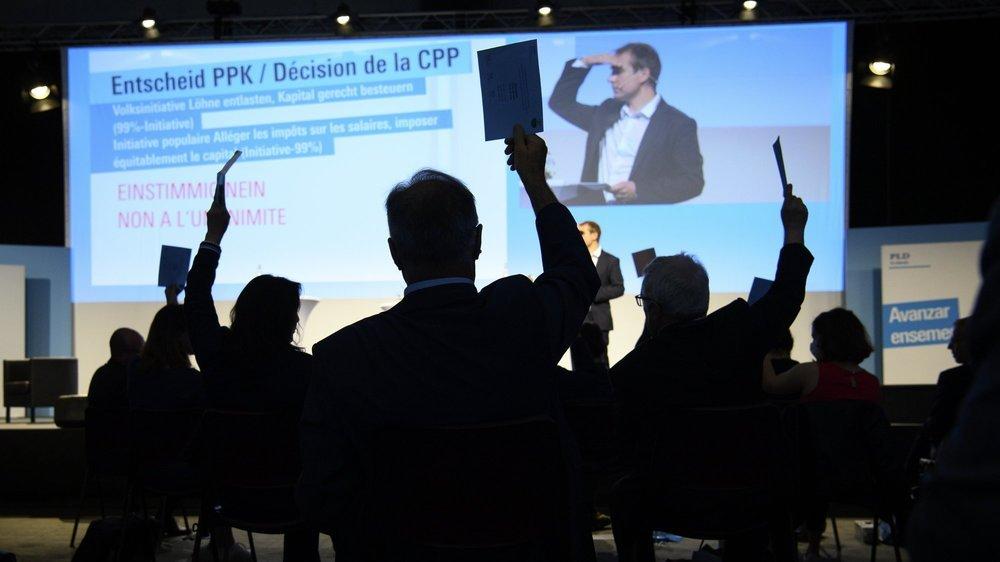A la demande de Philippe Nantermod, conseiller national PLR valaisan et maître de cérémonie, des délégués votent à main levée lors de l'assemblée du PLR Suisse ce samedi 3 juillet à Martigny.