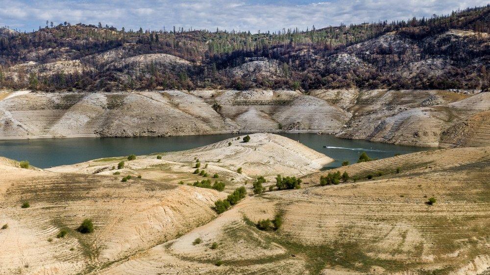 Un bateau traverse le lac Oroville sous les arbres brûlés par l'incendie 2020 North Complex Fire, à Oroville, en Californie. Le réservoir est à 39% de sa capacité et à 46% de sa moyenne historique.