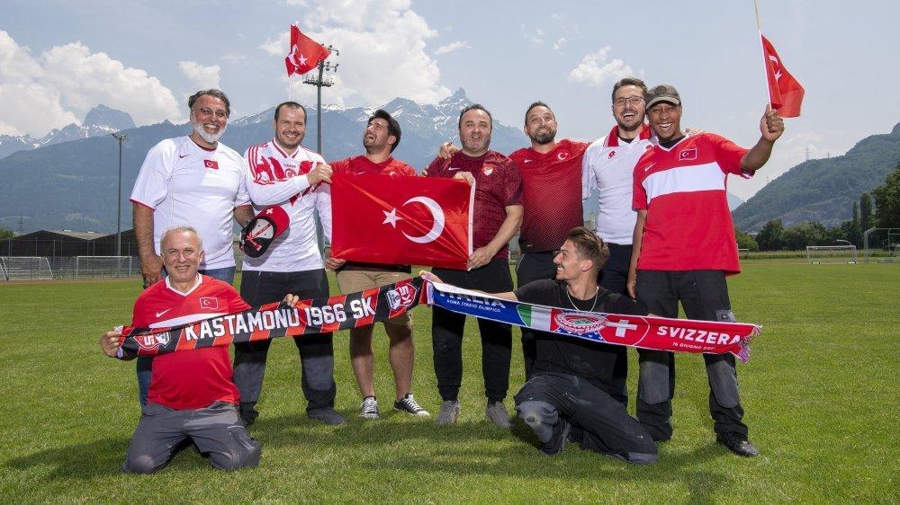 Les supporters turcs posent fièrement avec le maillot de leur équipe nationale sur la pelouse du Verney à Monthey malgré la déception des deux premiers matchs de leur équipe à l'Euro.