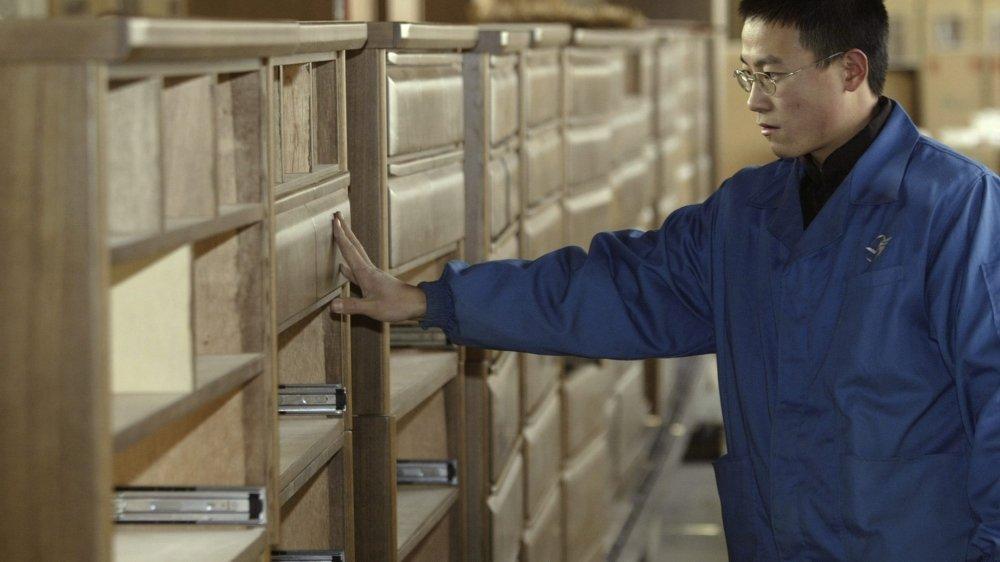 Un ouvrier vérifie la qualité d'une commode sur une ligne de production de meubles destinés à l'exportation dans la province de Hebei au nord de la Chine.