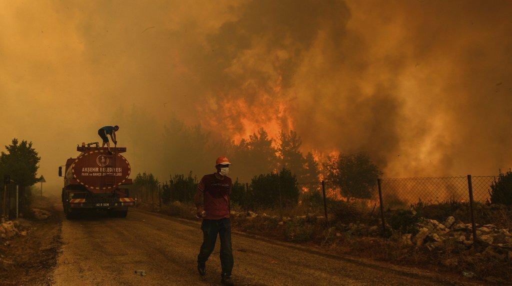 Un homme descend une route dans le village de Sirtkoy ravagé par le feu, près de Manavgat, en Turquie. Plus de 100 incendies de forêt ont été maîtrisés en Turquie, selon les autorités.