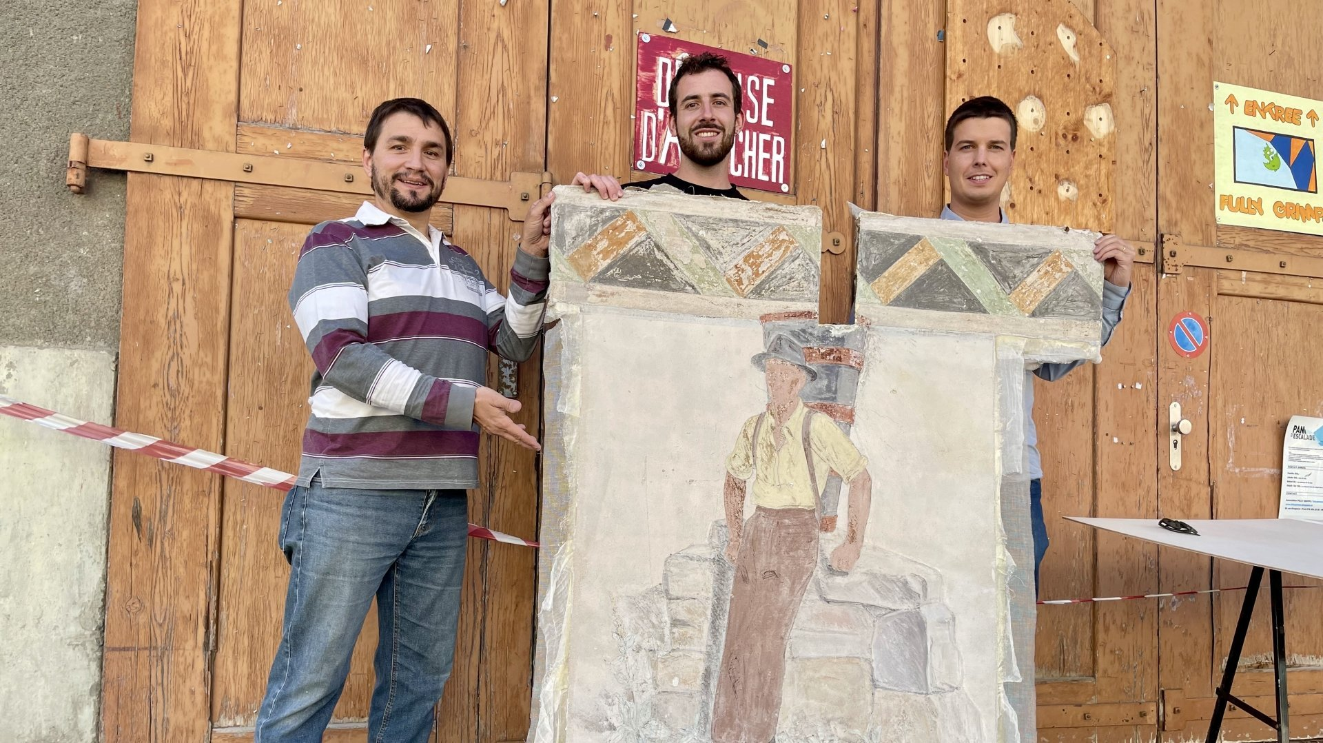 Alain Léger, Sébastien Grau et Alexandre Roduit présentent le premier tronçon de la fresque à avoir été sauvé. On ne voit ici que le dos – terne – de la peinture.