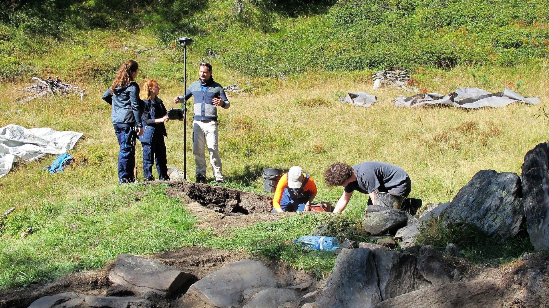 Au premier plan, les vestiges d'un four utilisé pour extraire le fer de la roche. Au deuxième plan, l'équipe de Rouven Turck s'attelle à extraire des scories et des morceaux de charbon de bois qui seront ensuite datés.