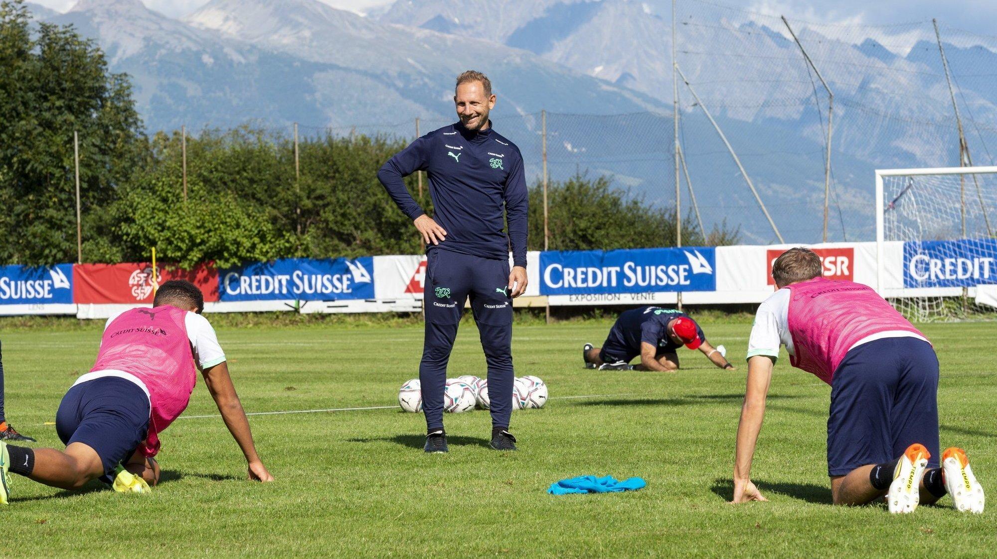 Mauro Lustrinelli supervise avec le sourire les exercices d'étirement des joueurs de l'équipe de Suisse des moins de 21 ans sur le terrain du Christ-Roi à Lens.