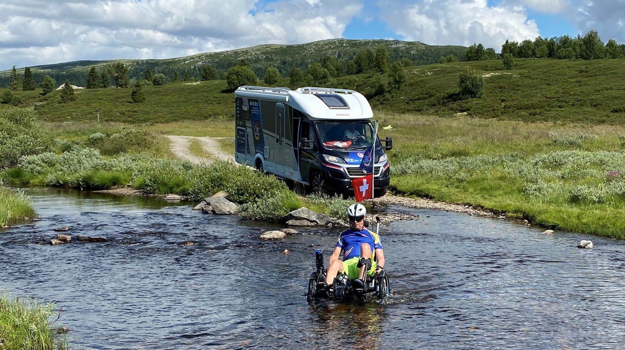 Christian Salamin, suivi par son camping-car, traverse une étendue d'eau.