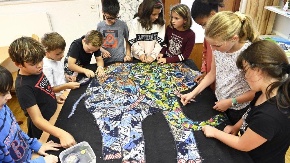 Les enfants de l'école confectionnent ensemble deux éléphants en patchwork.