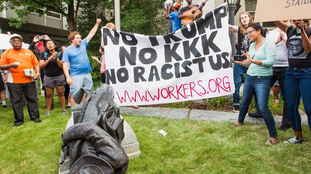 La statue d'un soldat du Sud sécessioniste a été mise à terre à Charlottesville, devant une banderole rejetant Donald Trump, le Ku Klux Klan et le racisme, signe que les Etats-Unis sont en pleine tourmente raciale.
