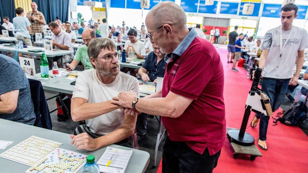Le président du CO Francis Niquille (àdroite) félicite le champion du monde 2017 de scrabble francophone, le Néo-Zélandais Nigel Richards.