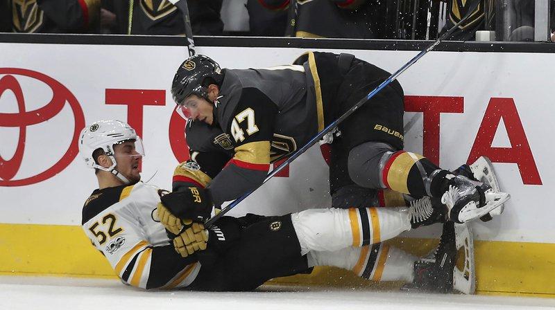 Sean Kuraly, le numéro 52 des Boston Bruins en train de subir la défense ferme de Luca Sbisa des Vegas Golden Knights.