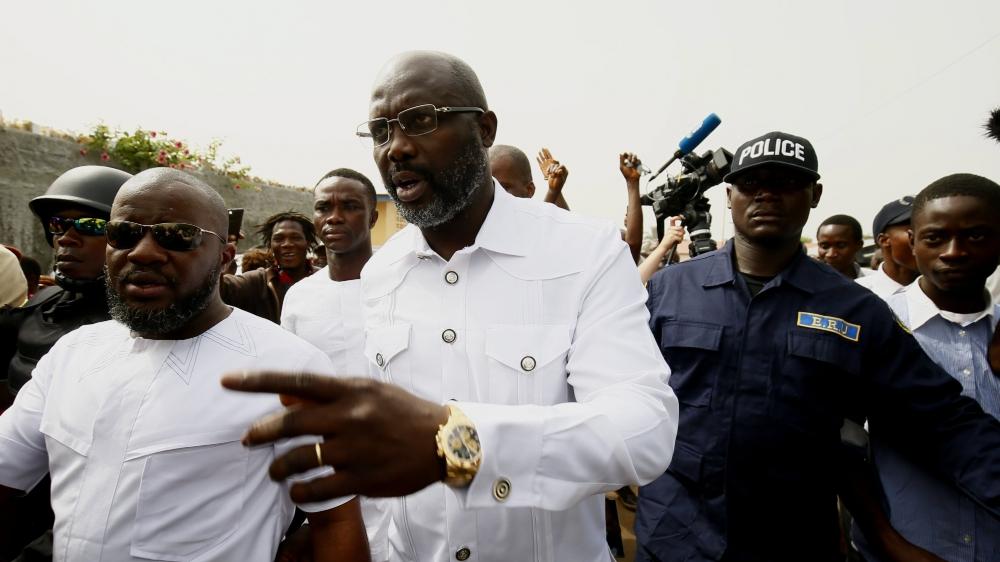 George Weah (au centre), hier à Monrovia, quelques minutes après avoir déposé son bulletin dans l'urne.