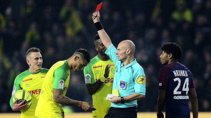 Football: un arbitre français, Tony Chapron, tacle un joueur lors de Nantes - PSG, puis il l'expulse