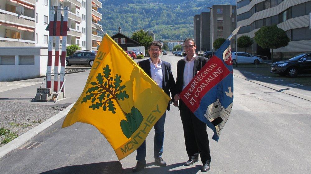 Yannick Buttet, président de Collombey-Muraz et Stéphane Coppey, président de Monthey, prennent la pose avec le drapeau de leur voisin.