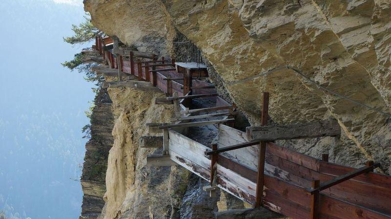 Le bisse d'Ayent a été tracé au flanc de la montagne. Les randonneurs empruntent une grotte pour franchir certains obstacles.