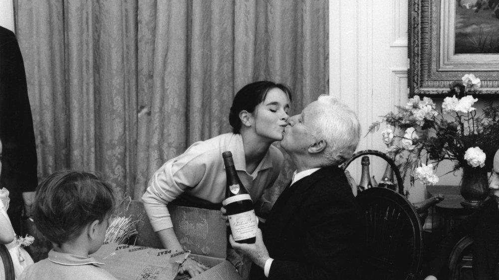 Charlie Chaplin embrassé par sa fille Géraldine à l'occasion de ses 70 ans célébrés au Manoir de Ban le 16 avril 1959.