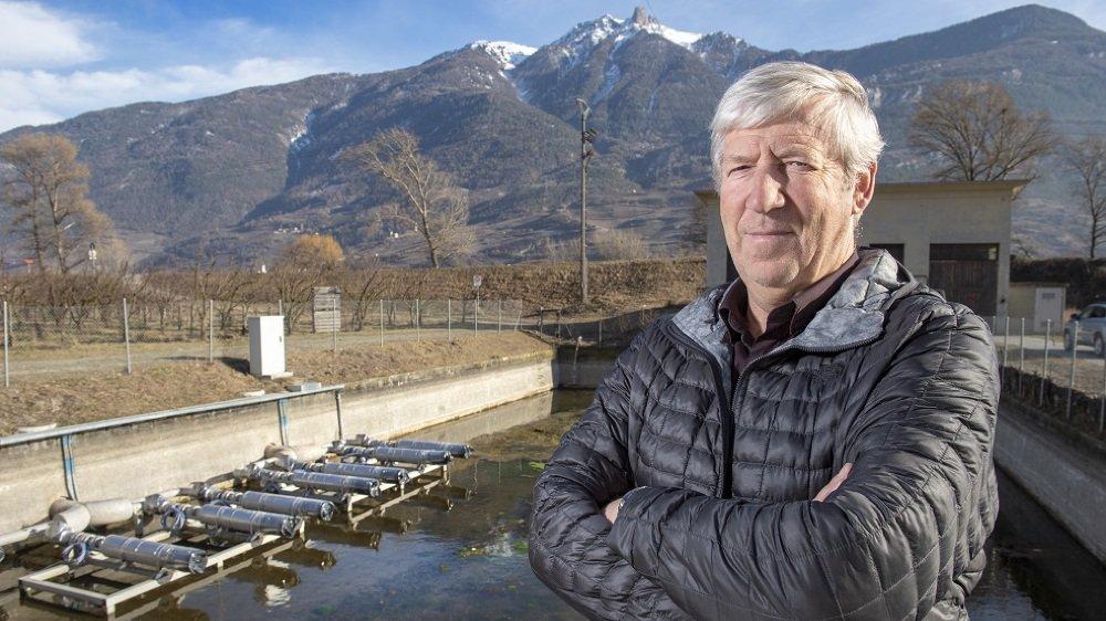 Président du consortium du Grand Blettay, Paul-Marie Dorsaz pose devant le bassin de rétention désormais muni de pompes pour alimenter le réseau destiné à l'aspersion des cultures.