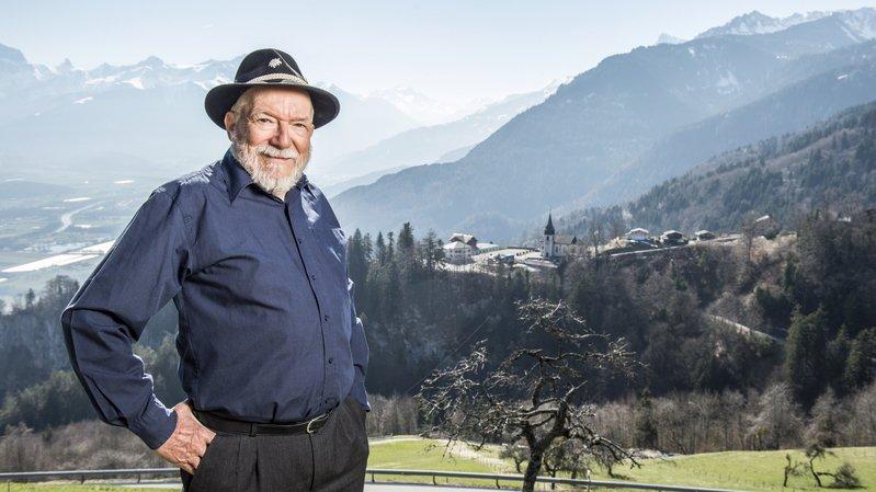 Michel Neuhaus apprécie le coup d'œil sur les montagnes, la plaine du Rhône et le village de Revereulaz.
