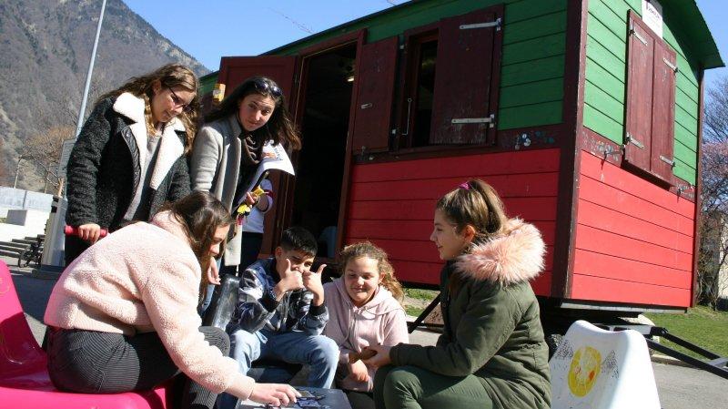 Les jeunes peuvent s'amuser et dialoguer autour de la roulotte stationnée dans la cour d'école.