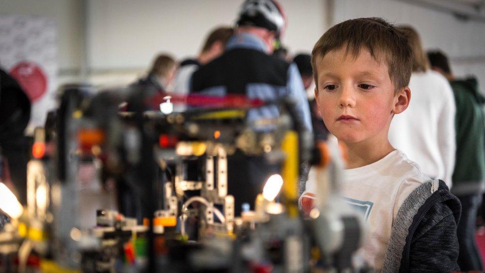 Un enfant captivé par un robot Lego capable de résoudre un rubik's cube.