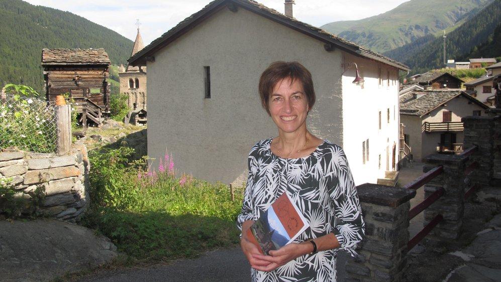 Comme le souligne l'historienne de l'art Marlène Hiroz, qui pose ici au sommet du village, devant l'ancien hôpital, le clocher de l'église et un grenier typique, Bourg-Saint-Pierre dispose d'un patrimoine bâti qui mérite le détour.