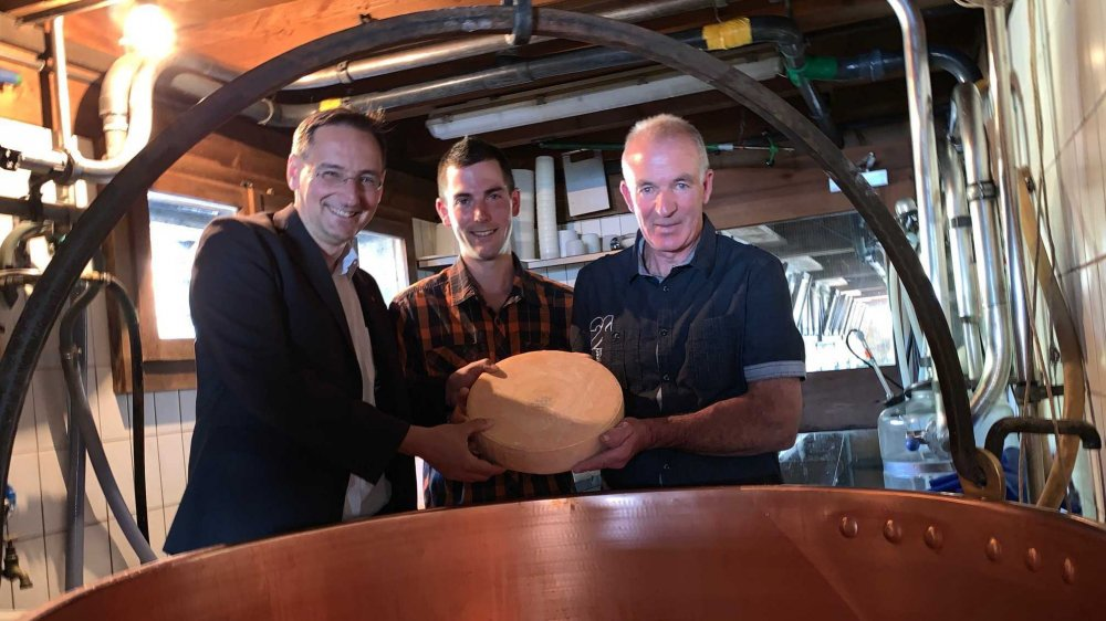 Le président de l'Interprofession Raclette du Valais AOP, Thomas Egger, le fromager Julien Mariétan et son père Serge, fiers de présenter le fromage qui a obtenu la note maximale de 20 sur 20