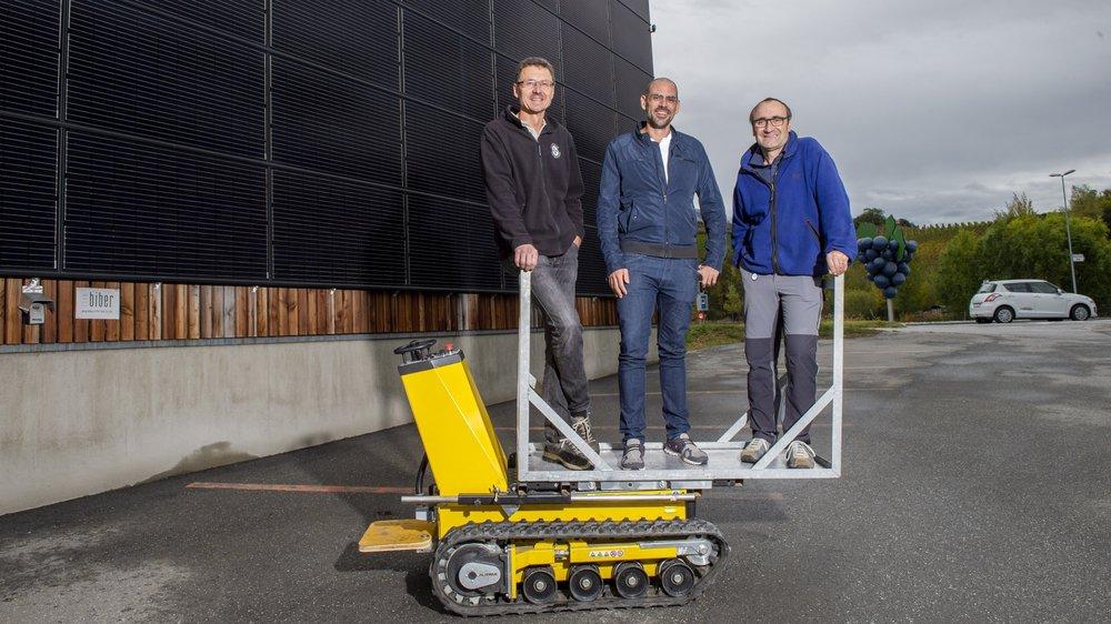 De g. à d.: Olivier Mounir, Jens Grichting et Philippe Constantin posent devant la façade de la halle de stockage de la Cave du Rhodan de Salquenen, recouverte de panneaux photovoltaïques.