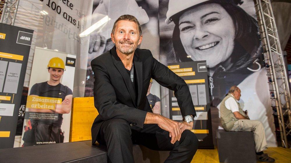 Serge Métrailler passe tout son temps sur le stand de l'AVE. Il pose devant le visage de Sandra Imboden, première femme entrepreneuse de la construction en Valais.
