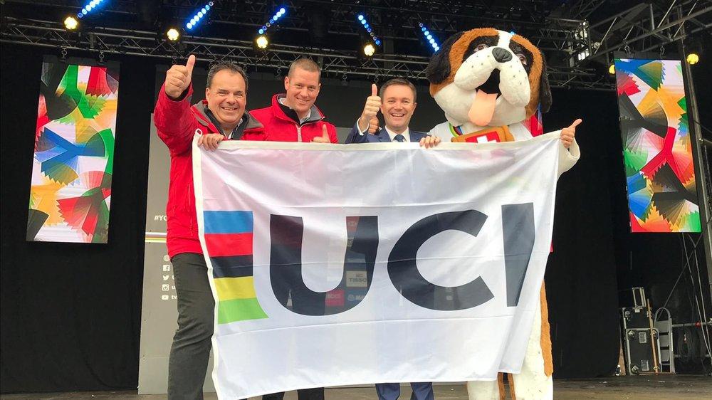 David Lappartient (troisième depuis la gauche) a remis le drapeau de l'UCI à Alexandre Debons et Grégory Devaud, les deux présidents du comité d'organisation, sous le regard de la mascotte, Barry.
