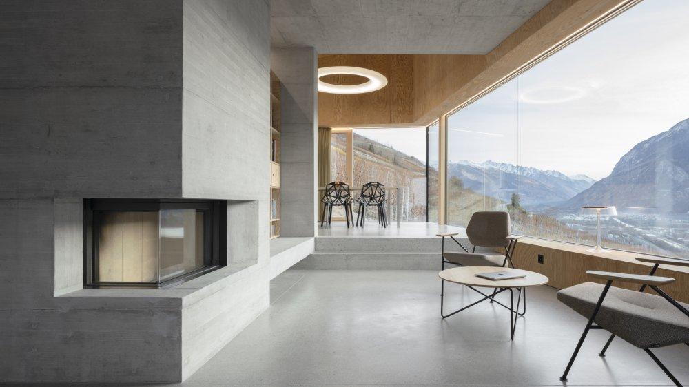 Bibliothèque et coin lecture assurent la transition entre séjour et cuisine. La régression progressive du béton au profit du bois et la différenciation volumétrique d'une pièce à l'autre distinguent spatialement les zones respectives.