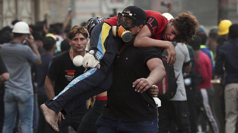 Un manifestant emmène un de ses camarades, blessé dans les affrontements avec les forces de l'ordre irakienne, à Baghdad