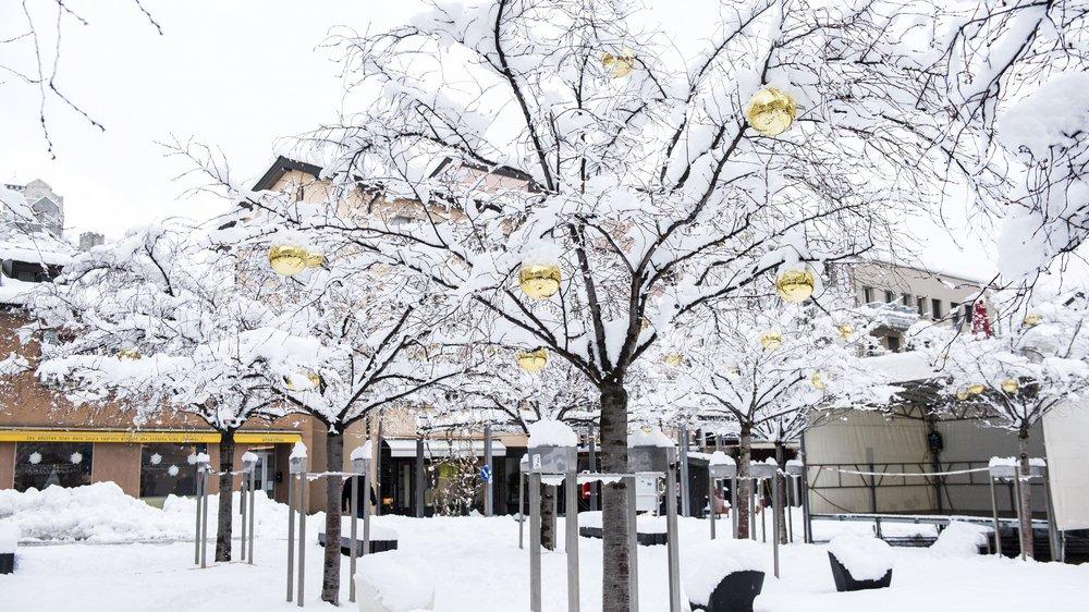 Cohabitation poétique entre les décorations de Noël et les pruniers japonais habillés de blanc à la place des Remparts à Sion.