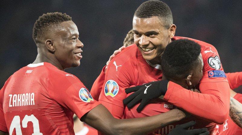 Denis Zakaria, à gauche et Manuel Akanji qui embrasse Breel Embolo, après un but contre le Danemark durant les qualifications pour l'Euro 2020.