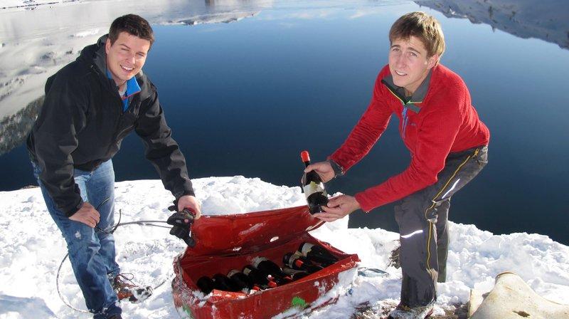 Sur les bords du Grand Lac de Sorniot, le vigneron Pierre-Elie Carron (à dr.) et le responsable de l'Office du tourisme de Fully Alexandre Roduit découvrent les bouteilles de petite arvine après leur séjour d'un an dans l'eau.