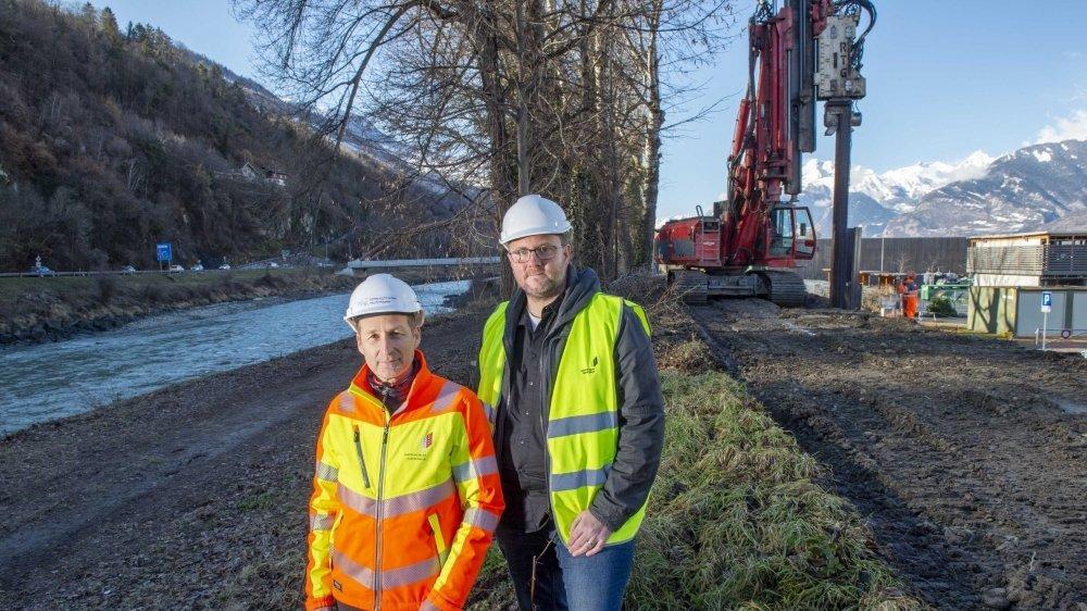 Toni Arborino, chef de l'Office cantonal de Rhône 3, et Didier Tille, responsable pour le Valais central, posent devant la machine qui enfonce les palplanches à l'intérieur de la digue existante. Ici, à la hauteur de la voirie de Sion.