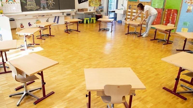 L'enseignante prépare sa classe en espaçant les tables.
