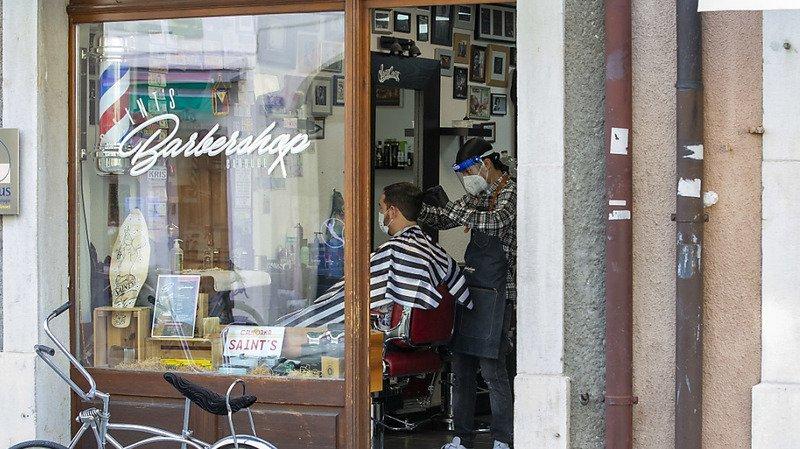 Coiffeurs et clients doivent désormais porter des masques, comme chez ce barbier, lundi, à Carouge. (Illustration)